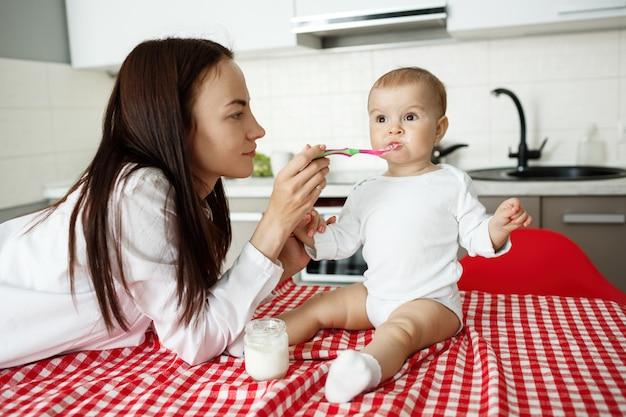 La madre alimenta lo yogurt del bambino sveglio con il cucchiaio
