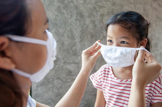 La madre asiatica aiuta sua figlia a indossare una maschera protettiva per proteggere la situazione dell'epidemia di covid-19 del coronavirus e l'inquinamento da smog dell'aria con pm 2.5