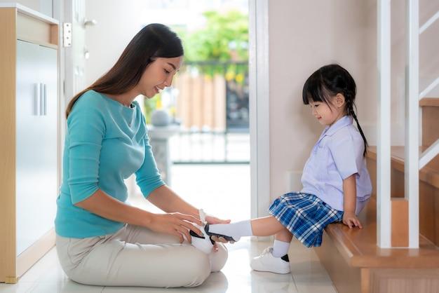 La madre asiatica che aiuta sua figlia a mettere le scarpe