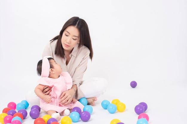 La madre asiatica e la neonata adorabile sono felici sulla parete bianca