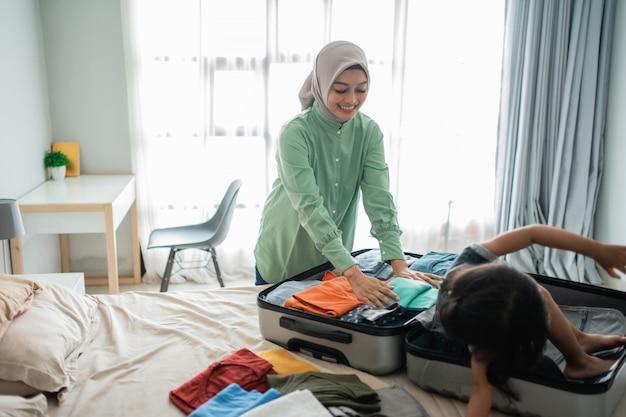 La madre asiatica prepara la valigia con sua figlia