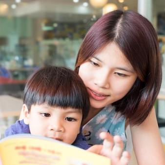 La madre asiatica sta leggendo suo figlio un libro divertente educativo.