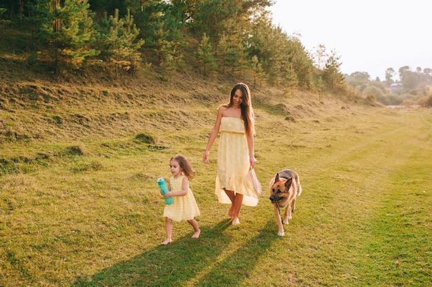 La madre cammina con la sua piccola figlia e il loro cane