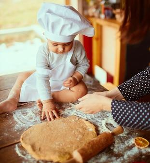 La madre con il figlio impasta l'impasto in cucina