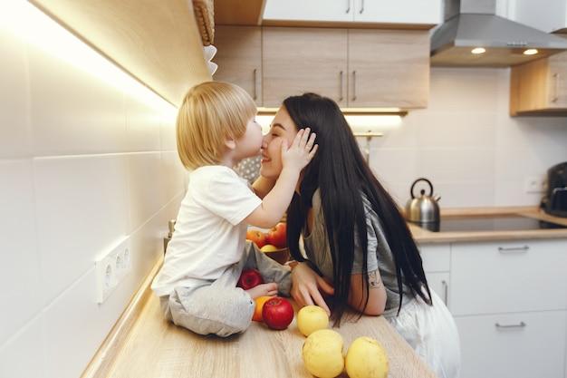 La madre con il piccolo figlio che mangia la frutta in una cucina
