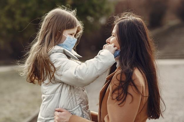 La madre con la figlia cammina fuori in maschere