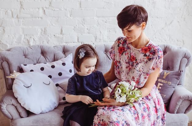 La madre con la figlia seduta sul divano