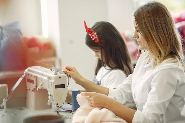 La madre con la piccola figlia cuce i vestiti nella fabbrica