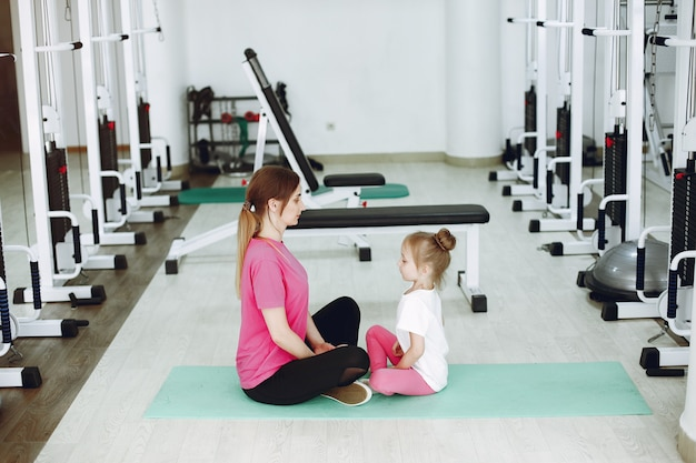 La madre con la piccola figlia è impegnata in ginnastica in palestra