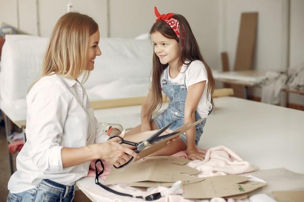 La madre con la piccola figlia misura il tessuto per cucire