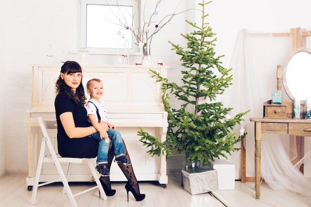 La madre con suo figlio che celebra le feste si avvicina all'albero di natale