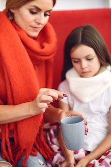 La madre dà a sua figlia malata il tè caldo