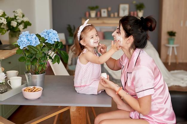 La madre della famiglia e la figlia del bambino nella mattina fanno colazione in cucina