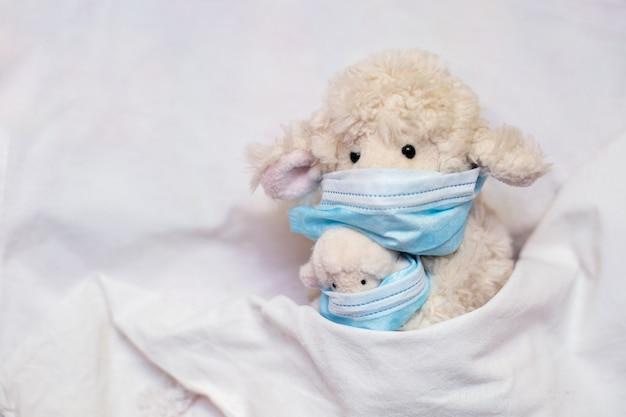 La madre delle pecore del piccolo giocattolo con l'agnello in mani si trova a letto. coronovirus, quarantena, epidemia, pandemia, influenza, raffreddore, malattia. concetto di medicina e salute.