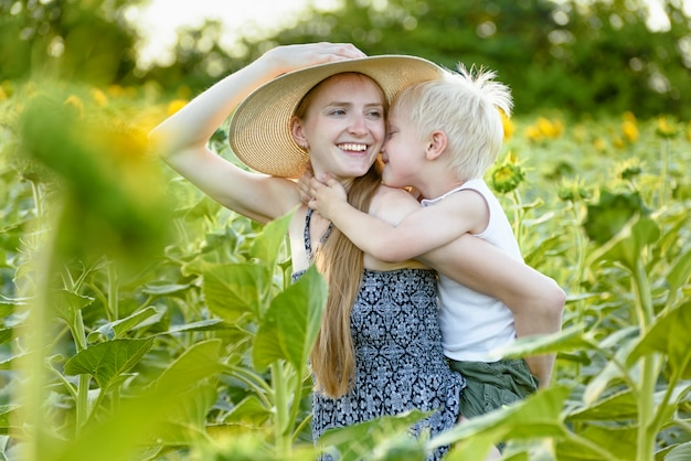 La madre di risata felice che dà al figlio del bambino guida sulle spalle del giacimento di fioritura verde dei girasoli
