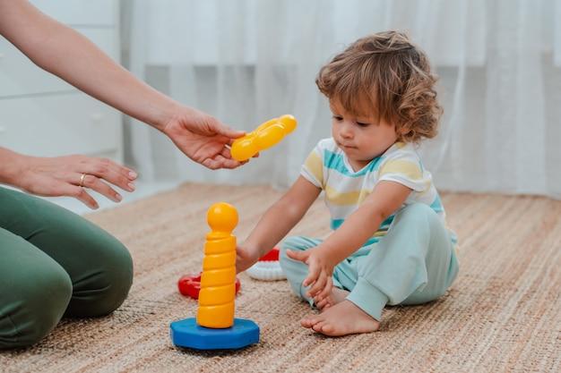 La madre e il bambino giocano sul pavimento nella stanza dei bambini. mamma e bambino piccolo stanno facendo con i giocattoli colorati di plastica.