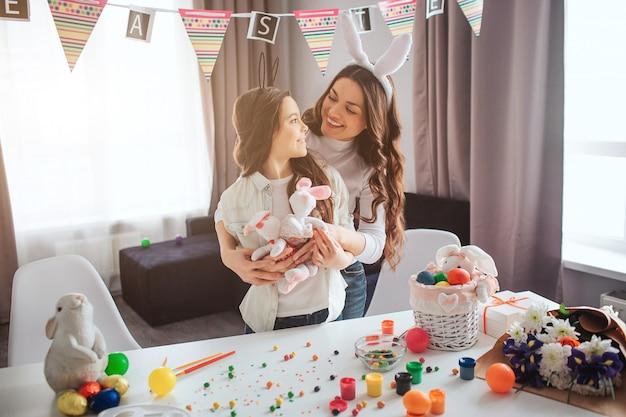 La madre e la figlia adorabili nella sala preparano per pasqua. si guardano e sorridono. abbraccio madre figlia. positivo e allegro.