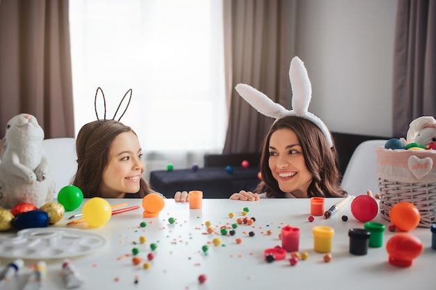La madre e la figlia allegre positive preparano per pasqua. giocano e si nascondono dietro il tavolo nella stanza. madre e figlia si guardano e sorridono. indossano orecchie da coniglio.