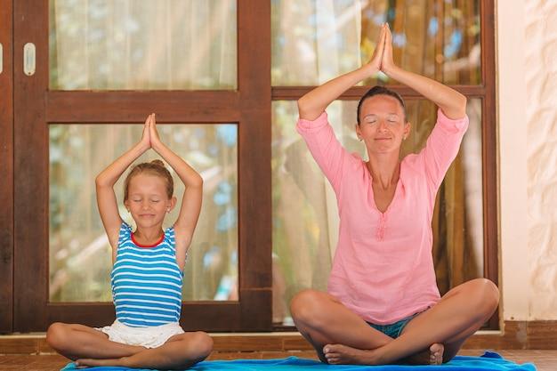 La madre e la figlia che fanno l'yoga si esercitano all'aperto