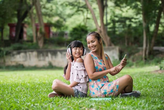 La madre e la figlia che leggono una fiaba a sua figlia ascoltano il suono con la cuffia nel parco