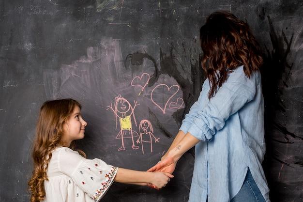 La madre e la figlia che si tengono per mano si avvicinano alla lavagna con l'illustrazione