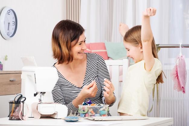 La madre e la figlia cucono i vestiti