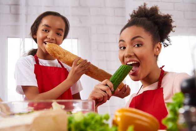 La madre e la figlia dell'afroamericano in grembiuli mangiano
