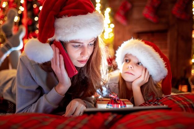La madre e la figlia della famiglia in cappelli e pigiami che scelgono i regali sulla compressa e sulla mamma digitali chiama il babbo natale dal telefono cellulare