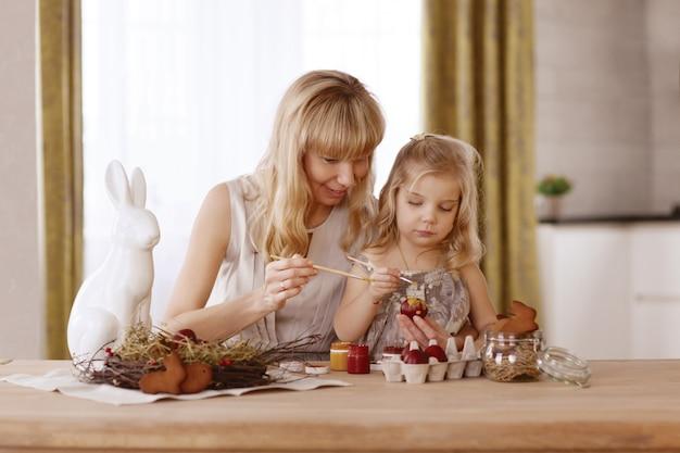 La madre e la figlia dipingono le uova di pasqua nella stanza alla tavola di festa.