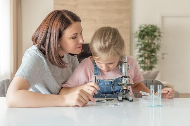 La madre e la figlia fanno esperimenti chimici con il microscopio a casa