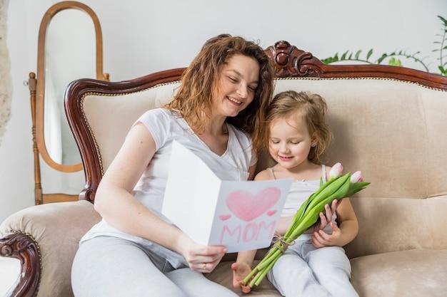 La madre e la figlia felici che leggono la cartolina d'auguri insieme nella casa con il tulipano fiorisce