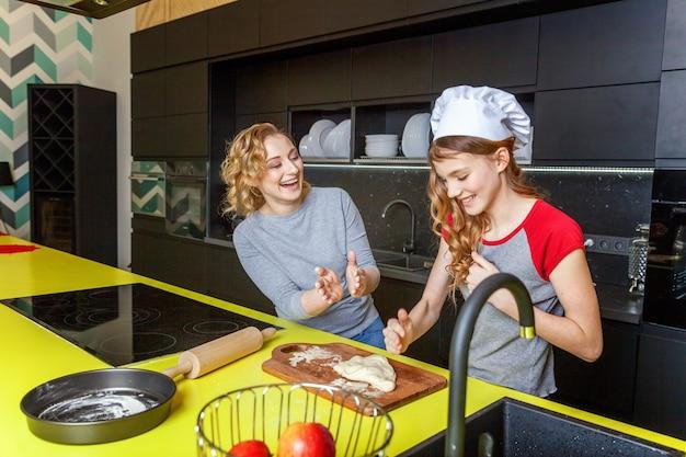 La madre e la figlia felici della famiglia che preparano la pasta, cuociono la torta di mele casalinga in cucina