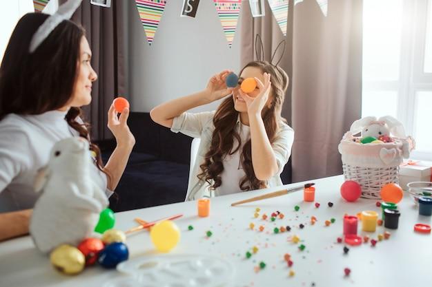 La madre e la figlia si preparano per pasqua. la ragazza tiene le uova variopinte negli occhi anteriori. la mamma fa lo stesso. loro si divertono. decorazione e pittura sul tavolo.