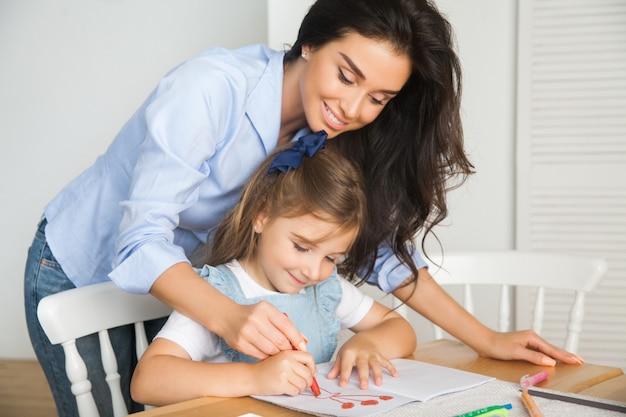 La madre e la figlia sorridenti stanno preparando per la scuola e sono impegnate nel disegno con le matite e le pitture