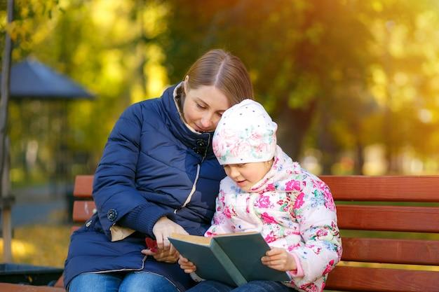 La madre e la figlia stanno leggendo il libro e si divertono in natura