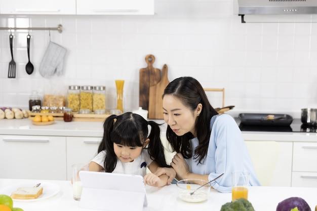 La madre e la figlia stanno mangiando la prima colazione e stanno guardando i media in una compressa