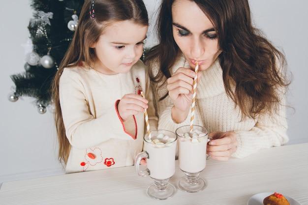 La madre e la piccola figlia bevono il cacao con le caramelle gommosa e molle