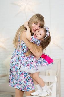 La madre e sua figlia con gli stessi vestiti giocano e si abbracciano