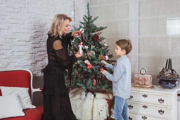 La madre e suo figlio sono a casa decorati per natale. tempo di miracoli di famiglia. buon natale e felice anno nuovo.