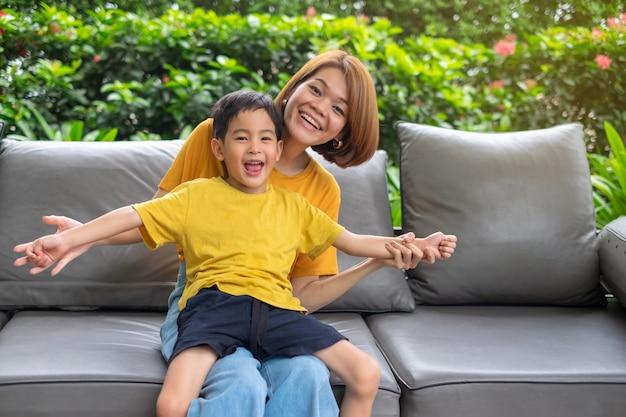 La madre ed il figlio asiatici felici ridono la seduta all'aperto
