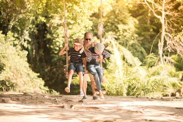 La madre ed il figlio giocano swing con felice insieme
