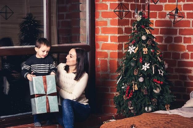 La madre fa un regalo a suo figlio per natale.