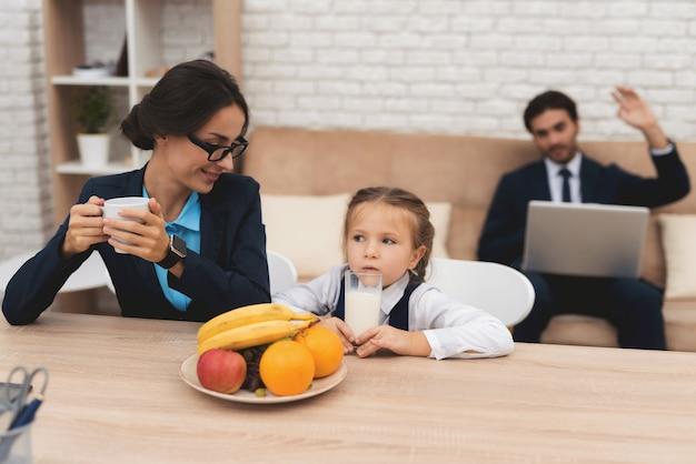 La madre felice beve il tè e il bambino offensivo beve il latte