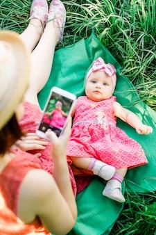 La madre felice che per mezzo del suo telefono con la sua famiglia della neonata all'aperto guarda dentro in un vestito rosa. outdoor ritratto di famiglia felice. aspetto familiare. emozioni, sentimenti, emozioni umane positive.