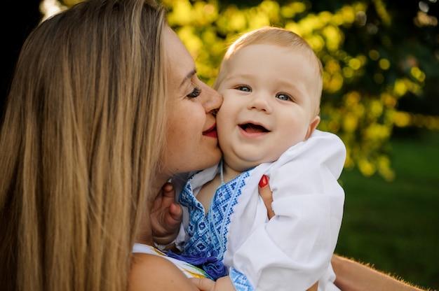 La madre felice che tiene sulle mani un neonato vestito con la camicia ricamata e lo bacia