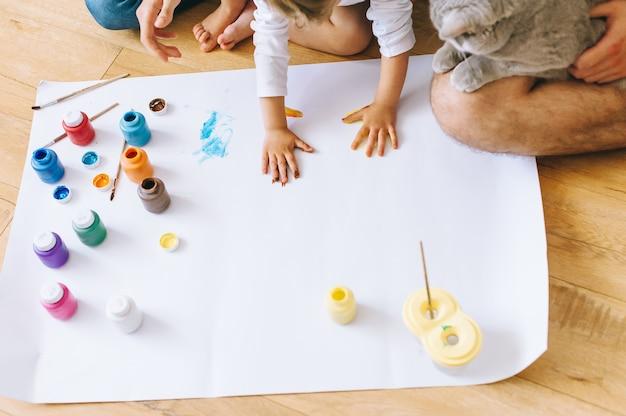 La madre felice del padre di arte della famiglia di gioia e le mani di manifestazione del figlio nei colori luminosi dipingono insieme l'arte dell'immagine di artgether dell'immagine