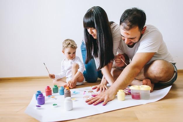 La madre felice del padre di arte della famiglia di gioia e le mani di manifestazione del figlio nei colori luminosi dipingono insieme l'arte dell'immagine