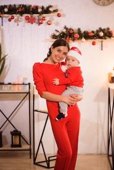 La madre felice e il bambino adorabile in cappello della santa celebrano il natale