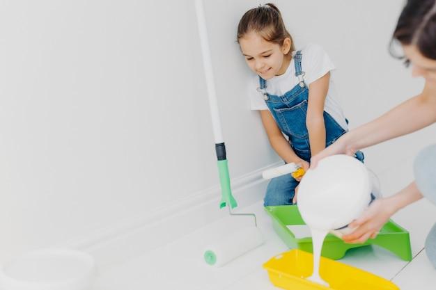 La madre felice e la piccola figlia fanno la riparazione a casa loro