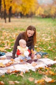 La madre felice e la piccola figlia stanno giocando nel parco di autunno.